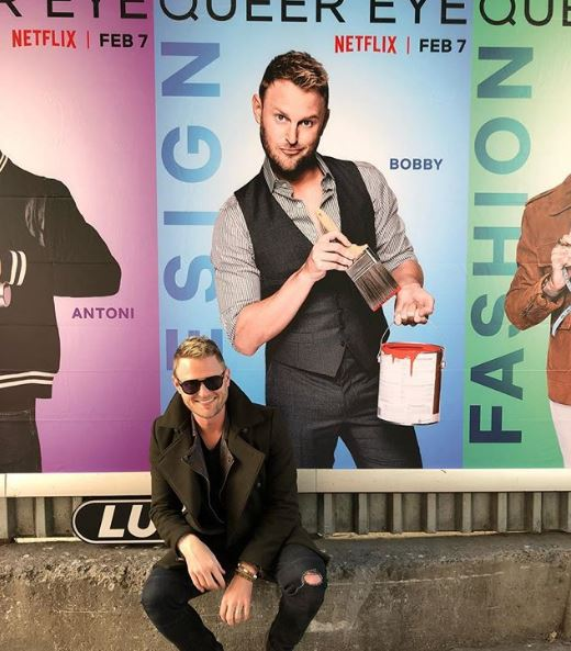 Bobby Berk taking picture in front of Queer Eye poster